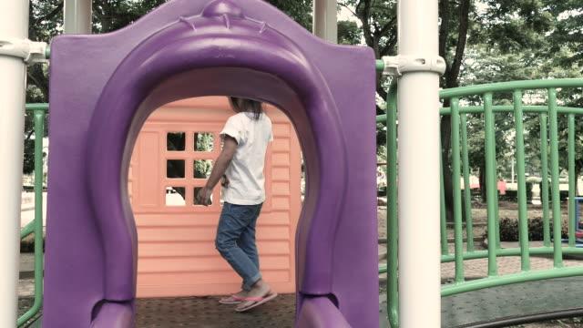 vídeos y material grabado en eventos de stock de pequeña niña está jugando en el patio de recreo. - estructura metálica para niños