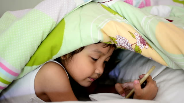 Little girl is playing game on the phone under the covers.