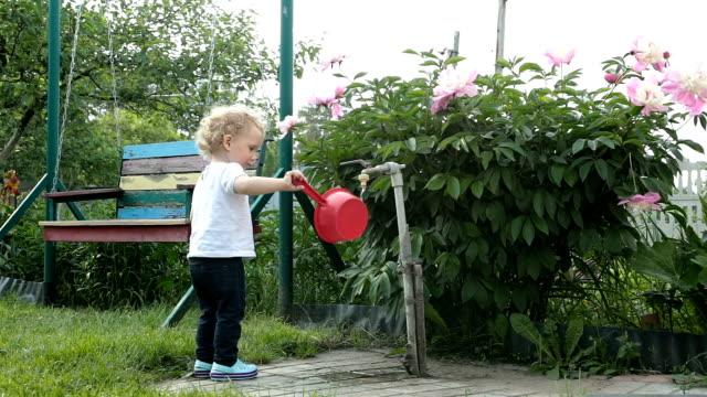 kleines mädchen spielt mit einer kelle für wasser. - gartengerät stock-videos und b-roll-filmmaterial