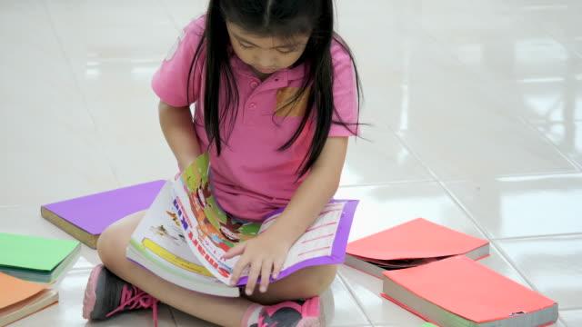 vídeos y material grabado en eventos de stock de la niña está leyendo un libro. - historia