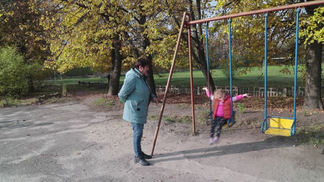 a little girl is riding a swing and her grandmother is watching her. - ukraine stock videos & royalty-free footage