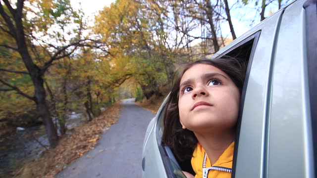 little girl is traveling looking from the car window - car interior stock videos & royalty-free footage