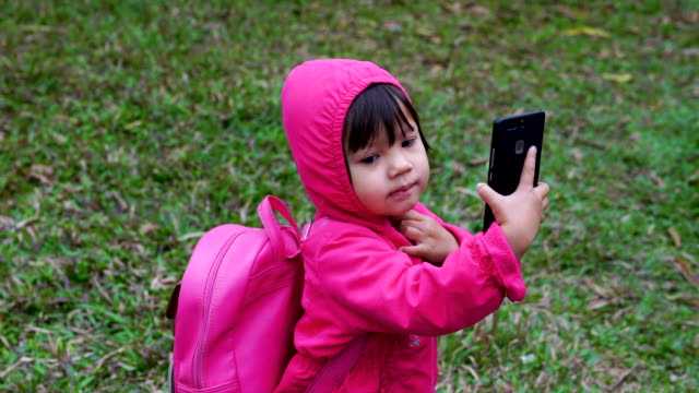 little girl is using a mobile phone after returning from school. - scolara video stock e b–roll