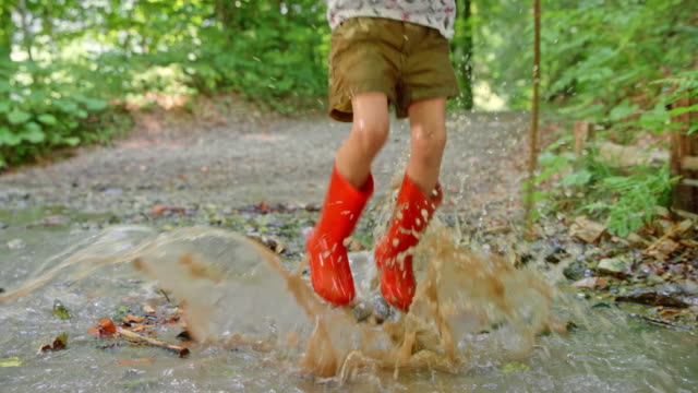 slo mo little girl jumping in a forest creek in red rain boots and smiling into the camera - wellington boot stock videos & royalty-free footage