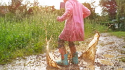 SLO MO Little girl jumping in a muddy puddle