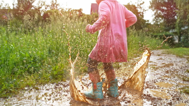 slo mo little girl jumping in a muddy puddle - trousers stock videos & royalty-free footage