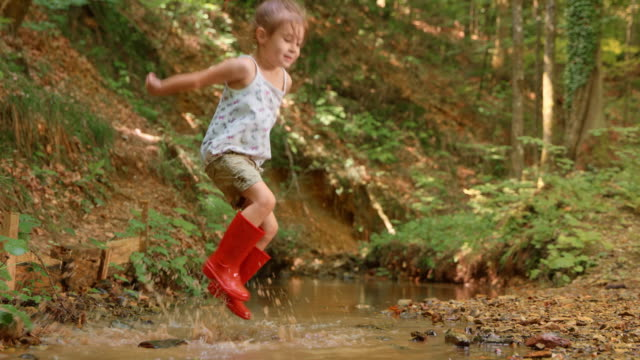 slo mo little girl jumping in a small creek in the forest wearing red rain boots - land stock videos & royalty-free footage