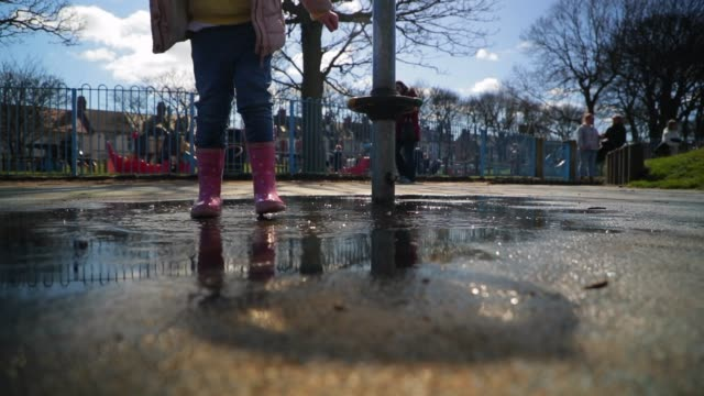 little girl jumping in puddle - stivale video stock e b–roll