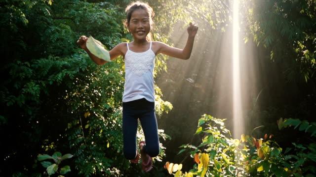 vidéos et rushes de petite fille sautant dans les jungles - indonésie