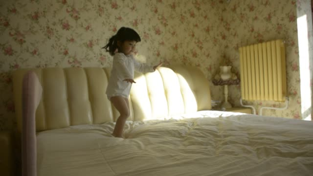 little girl jumping on bed - barefoot stock videos & royalty-free footage