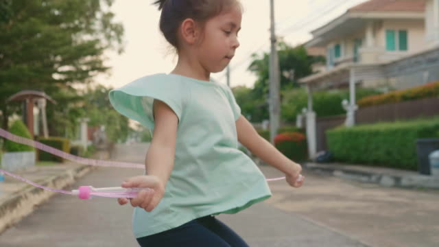 little girl jumping rope at sunset. slow motion - skipping along stock videos & royalty-free footage