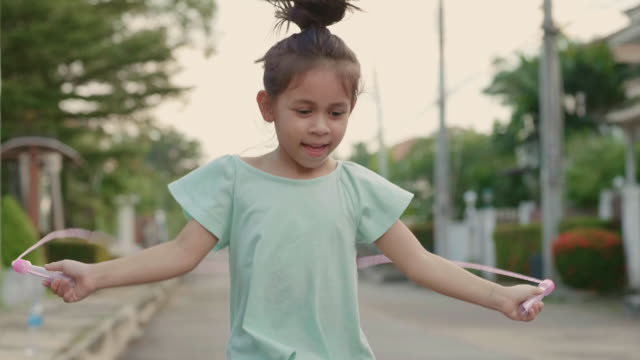 little girl jumping rope at sunset. slow motion - skipping stock videos & royalty-free footage