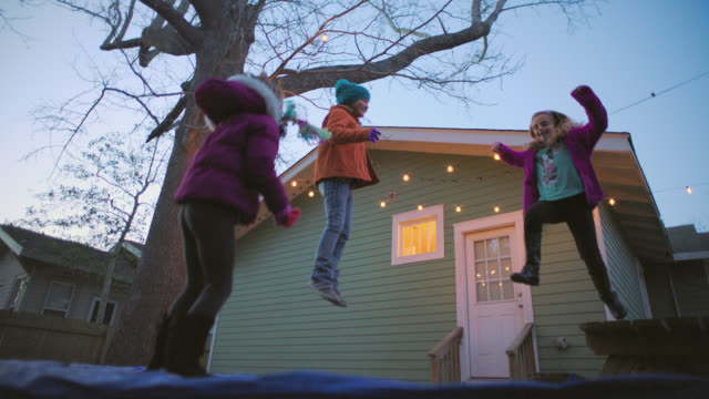 WS SLO MO. Little girl jumps onto trampoline and bounces up and down with friends in slow motion.