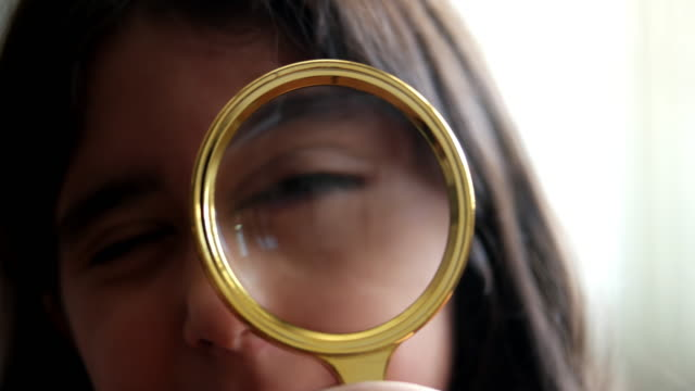 vídeos de stock e filmes b-roll de little girl kid looking through magnifying glass - lupa
