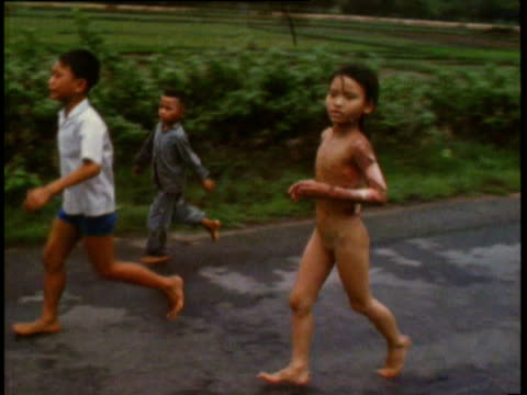 vídeos de stock, filmes e b-roll de / little girl kim phuc running past camera with napalm burns on back from bombing during vietnam war girl running with napalm burns on june 08 1972... - nu