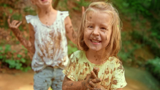 slo mo little girl laughing and enjoying playing with her friends in a forest creek while covered in mud - mud stock videos & royalty-free footage