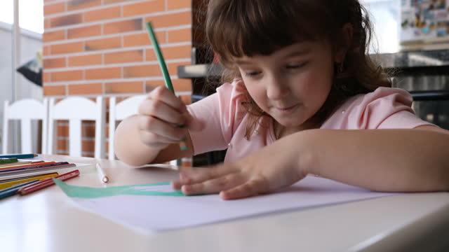 彼女の絵を考えて笑っている小さな女の子 - dia点の映像素材/bロール