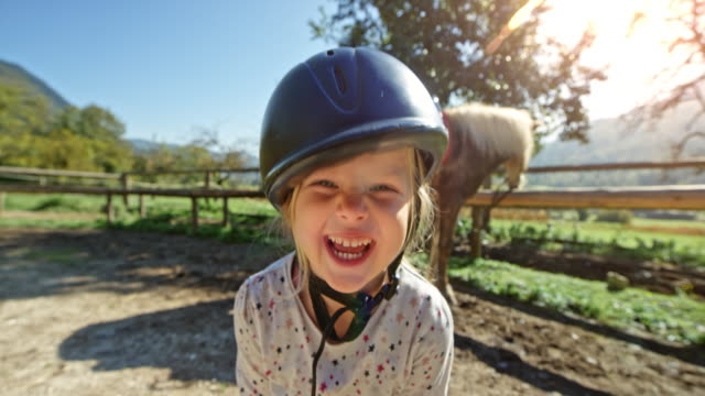 little girl laughing wearing a horse riding helmet and standing outside in the sun - sports helmet stock videos & royalty-free footage
