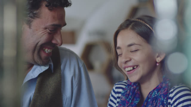 MS SLO MO. Little girl laughs with her dad on fun father daughter coffee shop date.