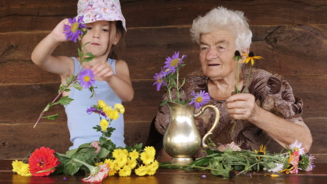 little girl learn how to arrange flowers in a vase. real people, rural scene. - bouquet stock videos and b-roll footage