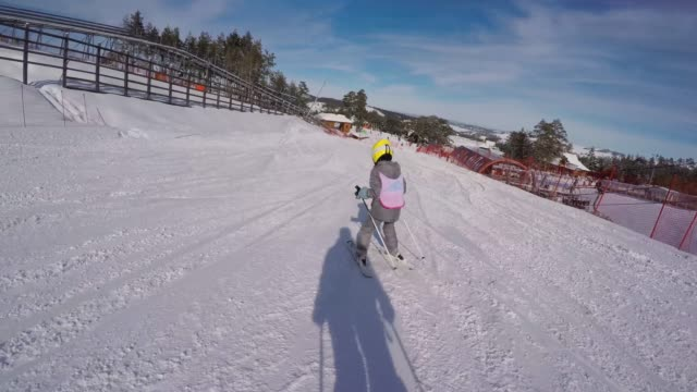vidéos et rushes de la petite fille apprend à skier avec l'instructeur de ski - enseigne