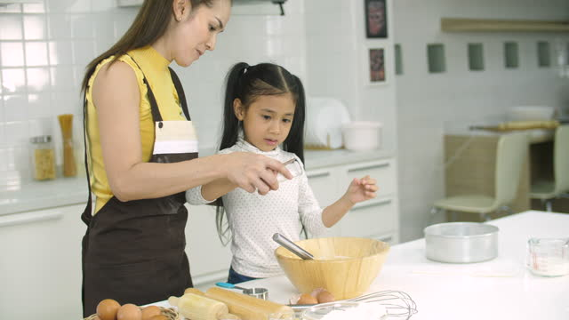 little girl learning baking with her mother - daughter stock videos & royalty-free footage