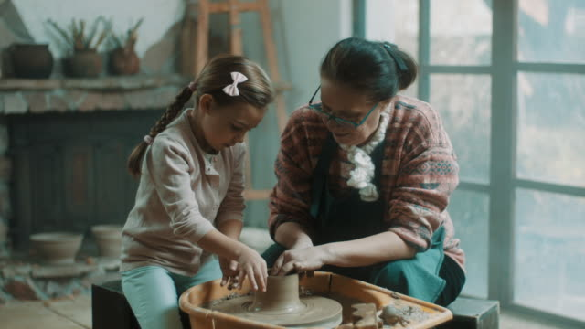 little girl learning how to use pottery wheel from pottery teacher - pottery stock videos and b-roll footage