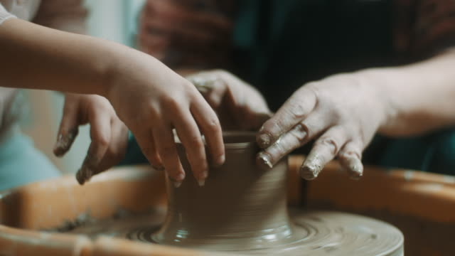 little girl learning how to use pottery wheel from pottery teacher - artista video stock e b–roll