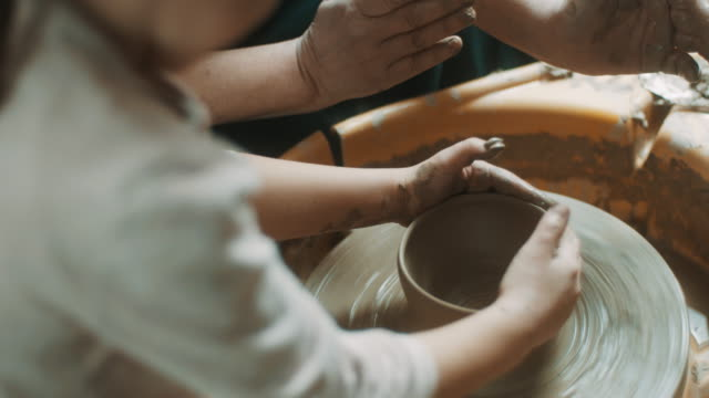 little girl learning how to use pottery wheel from pottery teacher - jug stock videos & royalty-free footage