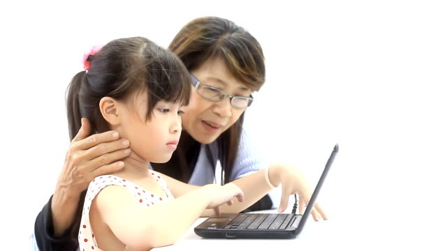 Little girl learning laptop with Grandmother.