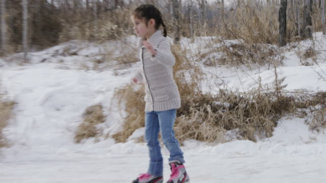 Little Girl Learning to Ice Skate on a Pond Outside