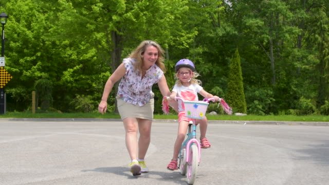 little girl learning to ride a bicycle. - helmet stock videos & royalty-free footage