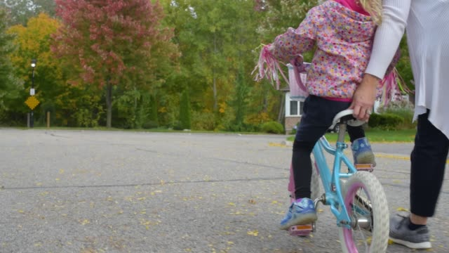 little girl learning to ride a bicycle - teaching stock-videos und b-roll-filmmaterial