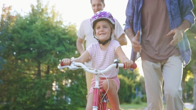 slo mo little girl learning to ride her bike with the help of granddad and father in sunshine - part of a series stock videos & royalty-free footage
