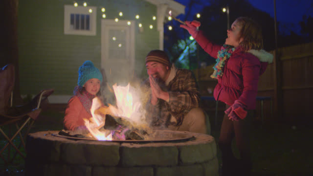 vídeos de stock, filmes e b-roll de ws. little girl lights stick and waves around flame while dad and sister warm hands by backyard fire pit. - artigo de vestuário para cabeça