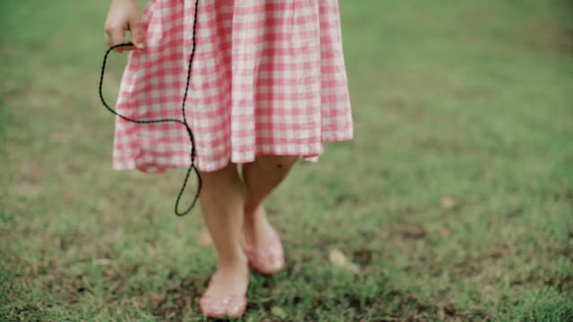 A little girl (5-7) listening to music and walking in field / Bangkok, Thailand