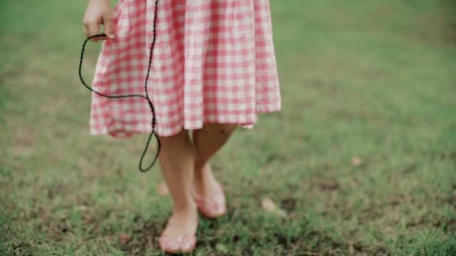 En liten flicka (5-7) Lyssna på musik och promenader i fältet / Bangkok, Thailand
