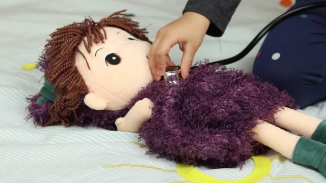 little girl listens to the doll's heart with a stethoscope - human gender stock videos & royalty-free footage
