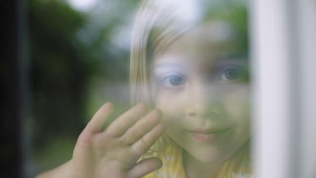slo mo. cu of little girl looking and waving at camera. - winken stock-videos und b-roll-filmmaterial