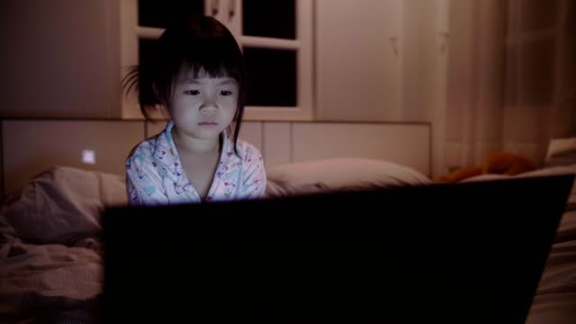 little girl(4-5 years) looking at laptop on bed at night - 4 5 years stock videos & royalty-free footage