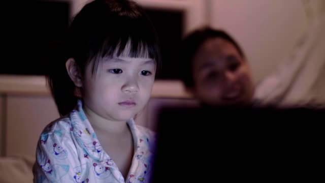 cu : little girl(4-5 years) looking at laptop on bed - 4 5 years stock videos & royalty-free footage