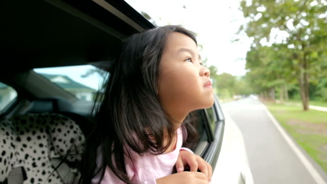 Little girl looking out from car