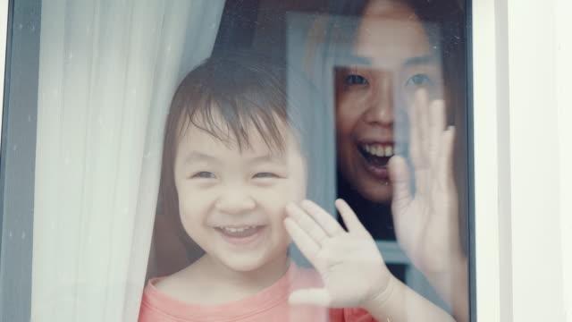 vídeos de stock e filmes b-roll de little girl looking out from window - etnia asiática