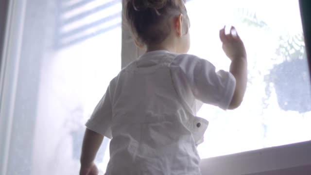 little girl looking outside the window and  waving - child waving stock videos & royalty-free footage