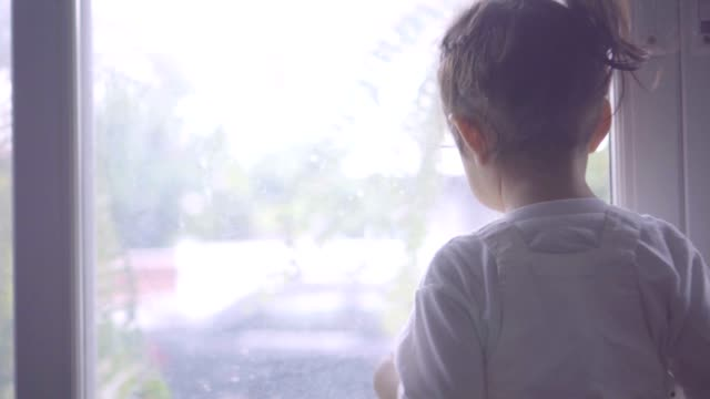 little girl looking outside the window - guardare in una direzione video stock e b–roll