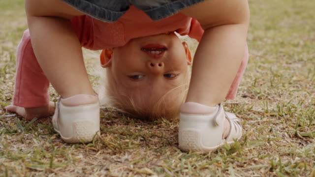 little girl looking to camera through her legs - upside down stock videos and b-roll footage