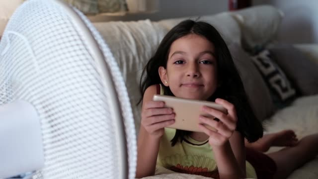 a little girl looks at her phone next to the fan one summer afternoon. - heat stock videos & royalty-free footage