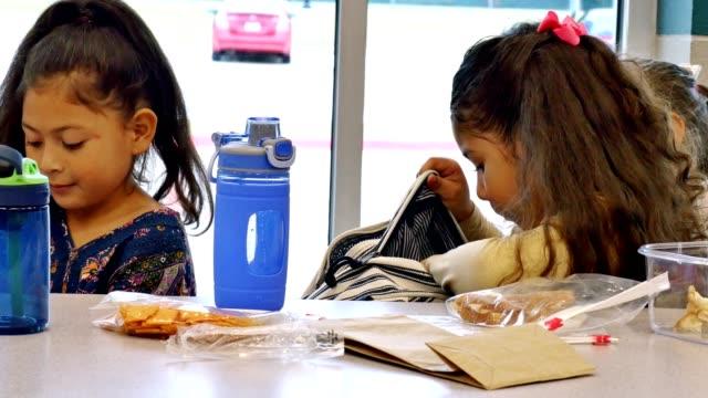 vídeos y material grabado en eventos de stock de niña mira en la mochila durante el almuerzo - mochila bolsa