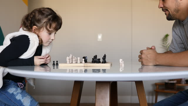 little girl losing a piece to her father in a chess game - dia stock videos & royalty-free footage