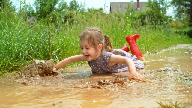 slo mo little girl lying in a puddle and moving her hands as if she were swimming - children stock videos & royalty-free footage